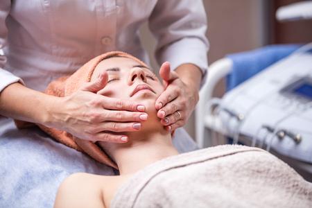 masaje: Mujer joven en el salón de spa, esteticista realizar masaje facial