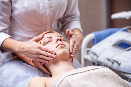 facial: Young woman in spa salon, beautician performing facial massage Stock Photo