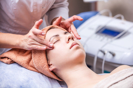 lifting: Young woman in spa salon, beautician performing facial massage Stock Photo