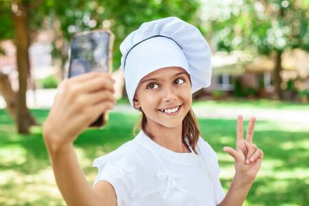 making a face: Happy girl in chefs hat making selfie Stock Photo