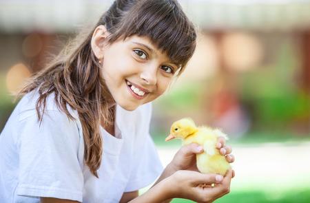 primavera: niña sonriente con un patito de primavera Foto de archivo