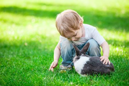 Jongetje spelen met konijn. Konijn in focus.