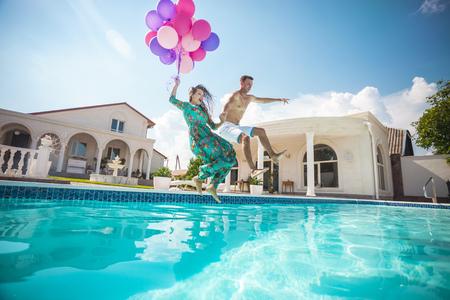 estilo de vida: Feliz jovem casal pulando na piscina, segurando um monte de balões