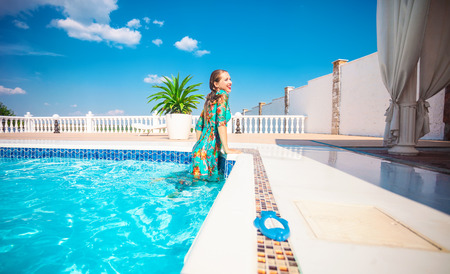 Happy young woman getting out of a swimming pool. The woman is wearing a dress. Stock Photo
