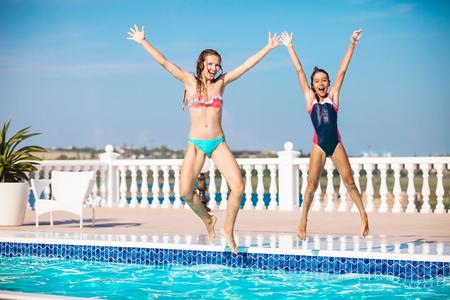 traje de bano: Joven madre y su hija que saltan en la piscina y gritando de alegría