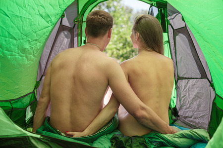 naked: Rear view of a naked young couple sitting in a tent Stock Photo
