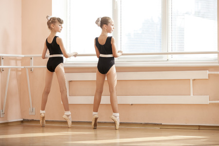 ballerina shoes: Young ballerinas standing on poite at barre in ballet class Stock Photo