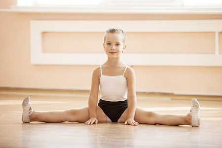 little girl dancing: Young girl doing splits while warming up at ballet dance class Stock Photo