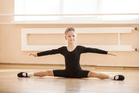 Boy dancer doing splits while warming up at ballet dance class Foto de archivo
