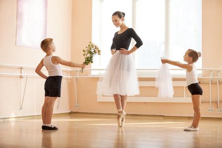 어린 소년과 그녀가 쁘 도중 춤을하는 동안 나이가 학생에게 꽃과 베일을주는 여자 : 발레 댄스 클래스에서 스톡 콘텐츠