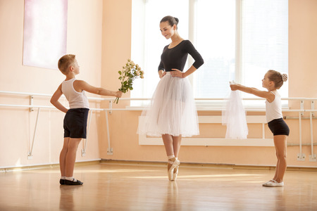 At ballet dancing class: young boy and girl giving flowers and veil to older student while she is dancing en pointe Banque d'images