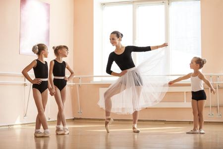 danza: Niña calentamiento y hablar con compañeros más jóvenes en la clase de baile del ballet