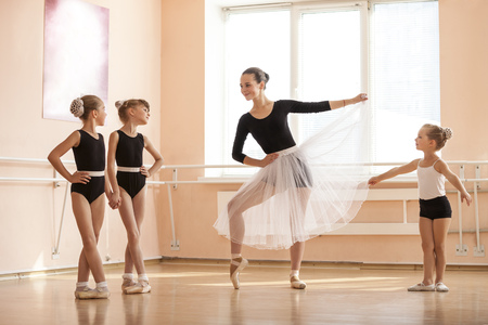 Young girl warming up and talking to younger classmates at ballet dancing class 스톡 콘텐츠