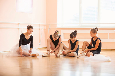 ballet: Young ballerinas putting on pointe shoes while sitting on floor in ballet class
