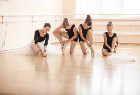 four classes: Young ballerinas putting on pointe shoes while sitting on floor in ballet class