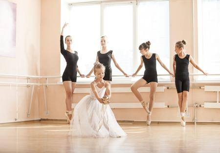 zapatos escolares: Baile de la ni�a con zapatos de punta, compa�eros de clase mayores calentamiento en los barres. En clase de baile de ballet.