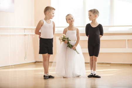 ballet hombres: At ballet dancing class: young boys and a girl with flowers posing gracefully