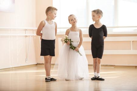 ballet hombres: En el ballet clase de baile: chicos jóvenes y una niña con flores posando con gracia