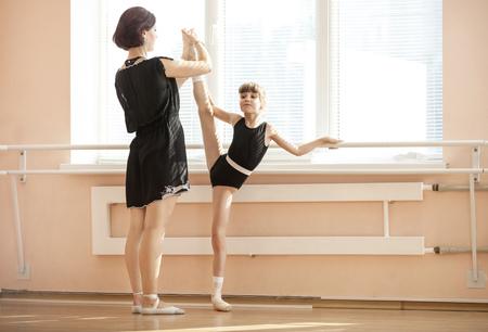 ballerina: Ballet teacher adjusting leg position of young ballerinas at barre