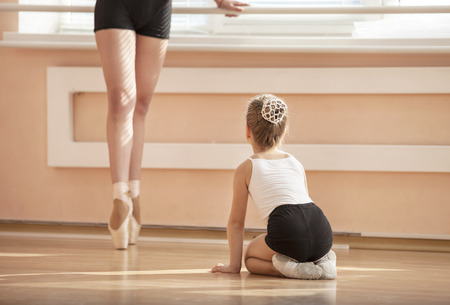 Girl beginner watching classmate standing en pointe in ballet dancing class Фото со стока