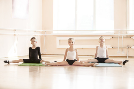 Young dancers doing splits while warming up at ballet class