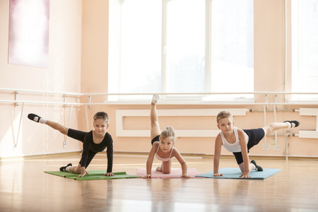 ballet hombres: Jóvenes bailarines que calientan en clase de ballet