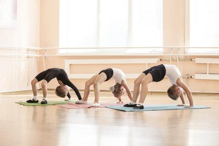 ballet: bailarines jovenes que realizan ejercicio de puente durante el calentamiento en la clase de ballet