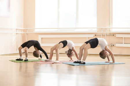 ballet hombres: Young dancers performing bridge exercise while warming up at ballet class