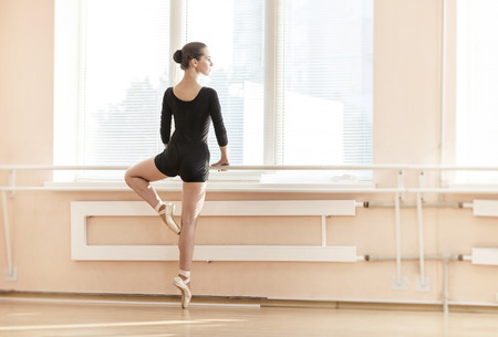 ballet dance: Young ballerina standing on poite at barre in ballet class