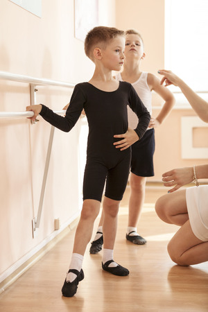 Young boys working at the barre in a ballet dance class. Teacher adjusting the position of one of them. Banque d'images