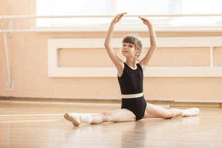 Young girl doing splits while warming up at ballet dance class Standard-Bild
