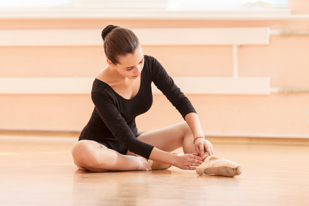 pointe shoes: Young ballet dancer putting on pointe shoes while sitting on floor
