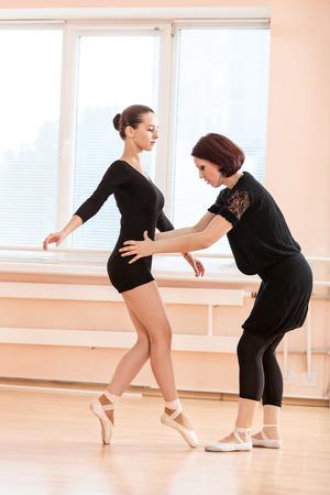 maestro: profesora de ballet ajustar la posici�n de las piernas de las bailarinas j�venes en barra