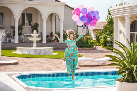 girl home: Joyful young woman jumping into the pool while holding a bunch of balloons