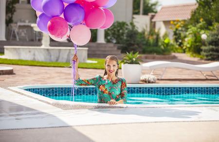 mojada: Mujer joven feliz que un manojo de globos después de saltar en una piscina en un vestido. Cumpleaños o celebración concepto del estado de ánimo.