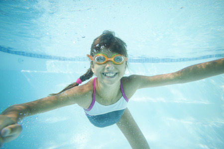 active kids: Joyful girl swimming underwater in pool