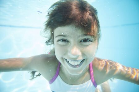 diving pool: Joyful girl swimming underwater in pool
