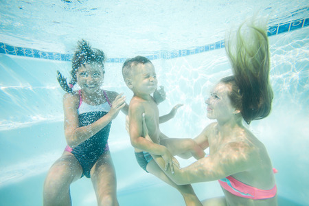 diving swimming pool: Happy family swimming underwater. Mother, son and daughter having having fun in pool. Stock Photo