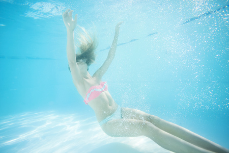 accidental: Young woman underwater in swimming pool. Danger of accidental falling into water. Stock Photo