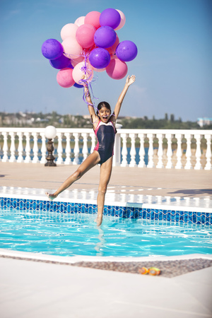swimming pool home: Joyful girl jumping into the pool while holding a bunch of balloons Stock Photo