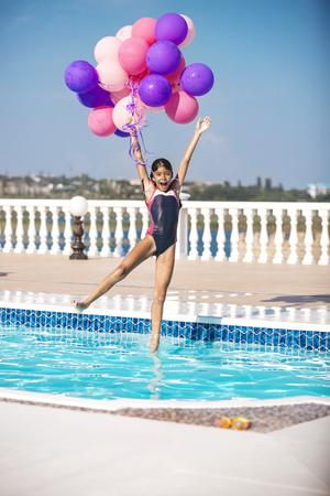 traje de bano: La muchacha alegre salta en la piscina mientras sostiene un manojo de globos