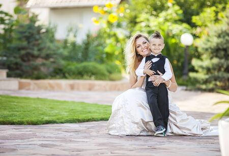 bride dress: Happy bride and smiling little boy outdoors