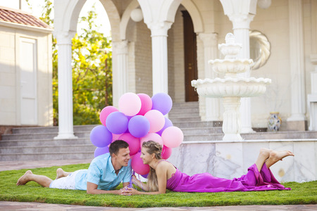 woman surprise: Happy young couple lying down on the lawn in front of their villa and holding colorful balloons