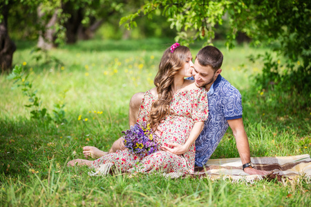 kissing pregnant belly: Happy young couple expecting baby, pregnant woman kissing her husband, sitting on green grass