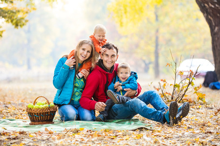 Happy young family with two boys in autumn forest photo