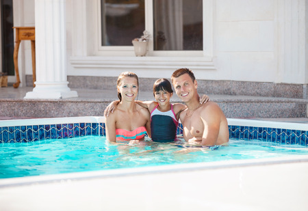guy portrait: Happy young couple and daughter in swimming pool near luxury villa Stock Photo