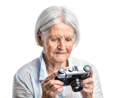 adult 80s: Senior woman with retro camera over white background Stock Photo