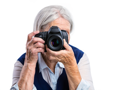 80s adult: Senior woman shooting with a digital camera over white background