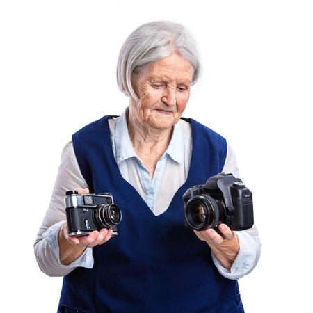 analogue: Senior woman choosing between old analogue camera and modern digital one
