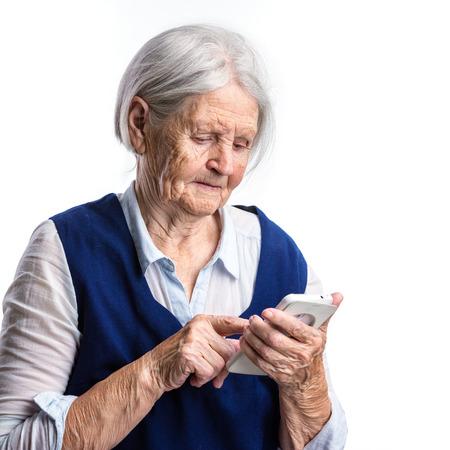 80s adult: Senior woman using smartphone over white Stock Photo